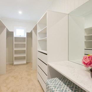 Diseño de armario vestidor unisex, minimalista, de tamaño medio, con armarios abiertos, puertas de armario blancas, moqueta y suelo beige