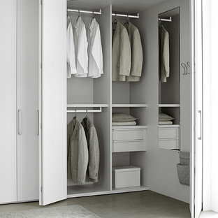 Inspiration for a large modern gender-neutral built-in wardrobe in New York with flat-panel cabinets, white cabinets and concrete floors.