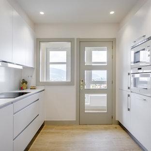 Modelo de cocina actual, grande, sin isla, con armarios con paneles lisos, puertas de armario blancas, suelo de madera clara, encimeras blancas, electrodomésticos con paneles y salpicadero blanco