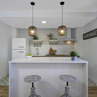 Foto de cocina de galera, campestre, pequeña, con fregadero encastrado, encimera de madera, salpicadero blanco, electrodomésticos blancos, una isla, suelo multicolor y encimeras marrones