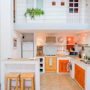 Foto de cocina comedor en L, mediterránea, pequeña, con fregadero de doble seno, puertas de armario naranjas, salpicadero blanco, salpicadero de vidrio templado, electrodomésticos blancos, península, encimera de cemento y suelo de travertino