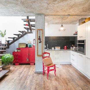 Imagen de cocina en L, ecléctica, sin isla, con armarios estilo shaker, puertas de armario blancas, salpicadero negro, electrodomésticos blancos, suelo de madera en tonos medios, suelo marrón y encimeras grises