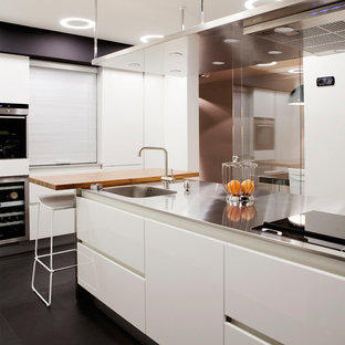 Photo of a modern kitchen in Other with an integrated sink, flat-panel cabinets, white cabinets, stainless steel benchtops, panelled appliances, porcelain floors and with island.
