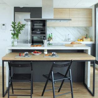 Foto på ett funkis turkos kök, med en undermonterad diskho, släta luckor, skåp i ljust trä, vitt stänkskydd, rostfria vitvaror, ljust trägolv, en köksö och beiget golv