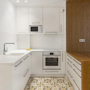 Foto de cocina en U, contemporánea, pequeña, con fregadero integrado, armarios con paneles lisos, puertas de armario blancas, salpicadero blanco, electrodomésticos blancos, suelo de baldosas de cerámica, península, suelo multicolor y encimeras blancas