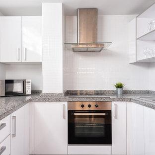 Imagen de cocina en U, actual, pequeña, con fregadero encastrado, armarios con paneles lisos, puertas de armario blancas, salpicadero blanco, electrodomésticos de acero inoxidable y encimeras grises