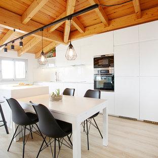Diseño de cocina comedor lineal, escandinava, de tamaño medio, con armarios con paneles lisos, puertas de armario blancas, salpicadero blanco, suelo de madera clara, una isla y suelo beige