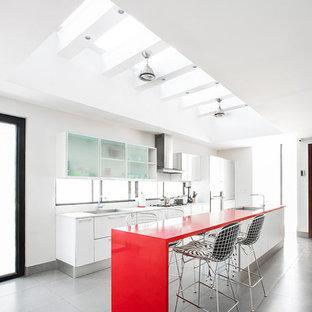 Modelo de cocina comedor de galera, contemporánea, con fregadero bajoencimera, armarios con paneles lisos, puertas de armario blancas, salpicadero blanco, salpicadero de vidrio, una isla, suelo gris y encimeras rojas