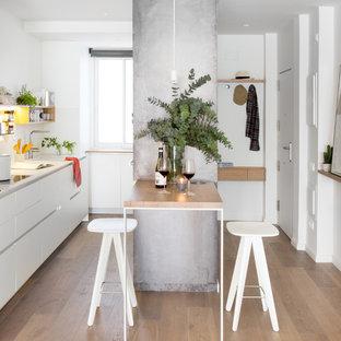 Imagen de cocina comedor lineal, nórdica, pequeña, con fregadero bajoencimera, armarios con paneles lisos, puertas de armario blancas, suelo de madera en tonos medios, península y salpicadero blanco