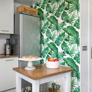 Imagen de cocina tropical, de tamaño medio, con armarios con paneles lisos, puertas de armario blancas, encimera de madera, una isla y encimeras marrones