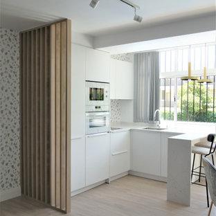 Diseño de cocina en U, actual, de tamaño medio, abierta, con fregadero de un seno, armarios con paneles lisos, puertas de armario blancas, electrodomésticos con paneles, península, suelo beige y encimeras blancas