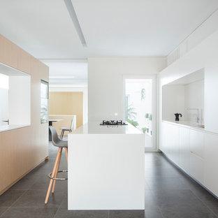 Imagen de cocina comedor de galera, minimalista, con armarios con paneles lisos, puertas de armario blancas, una isla, fregadero bajoencimera, salpicadero blanco, electrodomésticos con paneles, suelo gris y encimeras blancas