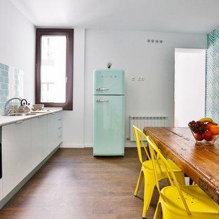 Ejemplo de cocina comedor lineal, contemporánea, de tamaño medio, sin isla, con fregadero de un seno, armarios con paneles lisos, puertas de armario blancas, salpicadero azul, salpicadero de azulejos de cerámica, electrodomésticos de colores y suelo de madera oscura