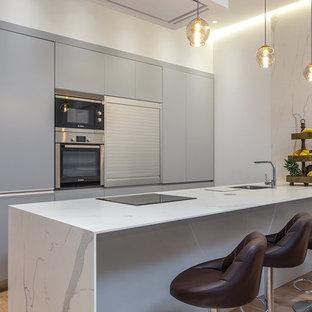 Imagen de cocina lineal, contemporánea, de tamaño medio, con armarios con paneles lisos, puertas de armario grises, encimera de mármol, suelo de madera en tonos medios, península, encimeras blancas, fregadero bajoencimera y electrodomésticos de acero inoxidable