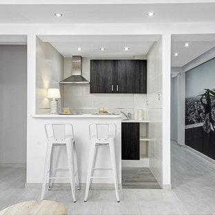 Modelo de cocina de galera, tradicional renovada, pequeña, abierta, con península, suelo blanco, armarios con paneles lisos, puertas de armario negras, encimeras blancas, salpicadero verde y electrodomésticos de acero inoxidable