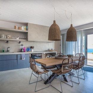 Foto de cocina comedor en L, mediterránea, de tamaño medio, sin isla, con puertas de armario azules, encimera de cemento, salpicadero verde, suelo de cemento, suelo gris y armarios con paneles lisos