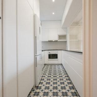 他の地域の小さいモダンスタイルのおしゃれなキッチン (アンダーカウンターシンク、フラットパネル扉のキャビネット、白いキャビネット、御影石カウンター、白いキッチンパネル、セラミックタイルのキッチンパネル、白い調理設備、セラミックタイルの床、アイランドなし、青い床、黒いキッチンカウンター) の写真