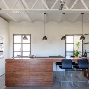 Modelo de cocina lineal, actual, grande, abierta, con armarios con paneles lisos, encimera de madera, electrodomésticos de acero inoxidable, suelo de cemento, una isla, suelo gris y puertas de armario de madera oscura