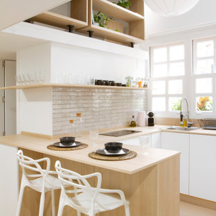 Design ideas for a scandinavian u-shaped kitchen in Madrid with a drop-in sink, flat-panel cabinets, white cabinets, wood benchtops, white splashback, light hardwood floors, a peninsula, beige floor and beige benchtop.