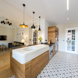 This is an example of a mid-sized contemporary galley open plan kitchen in Alicante-Costa Blanca with flat-panel cabinets, medium wood cabinets, white splashback, subway tile splashback, a peninsula, a farmhouse sink, marble benchtops, stainless steel appliances, terra-cotta floors and blue floor.