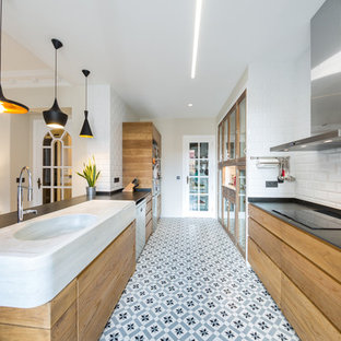 Photo of a mid-sized contemporary open plan kitchen in Alicante-Costa Blanca with flat-panel cabinets, marble benchtops, white splashback, ceramic splashback, stainless steel appliances, a peninsula, a single-bowl sink, light wood cabinets and multi-coloured floor.
