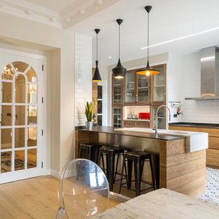 アリカンテの中くらいのコンテンポラリースタイルのおしゃれなキッチン (フラットパネル扉のキャビネット、中間色木目調キャビネット、白いキッチンパネル、サブウェイタイルのキッチンパネル、無垢フローリング、エプロンフロントシンク、大理石カウンター、シルバーの調理設備、青い床) の写真