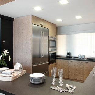 Imagen de cocina en U, contemporánea, de tamaño medio, cerrada, sin isla, con fregadero bajoencimera, armarios con paneles lisos, puertas de armario de madera oscura, encimera de acrílico y electrodomésticos de acero inoxidable
