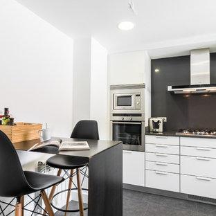 Imagen de cocina comedor lineal, contemporánea, pequeña, sin isla, con armarios con paneles lisos, puertas de armario blancas, salpicadero negro, electrodomésticos de acero inoxidable y suelo gris