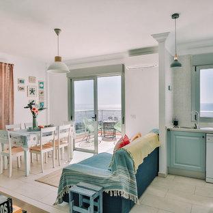 Ejemplo de cocina en L, clásica renovada, abierta, sin isla, con fregadero encastrado, armarios con paneles con relieve, puertas de armario azules, electrodomésticos blancos y suelo blanco