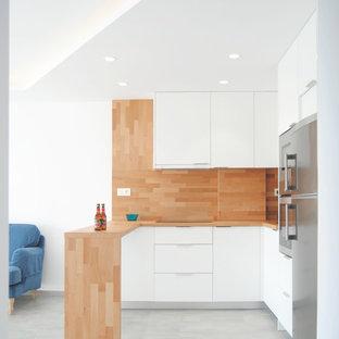 Ejemplo de cocina en U, marinera, de tamaño medio, abierta, con armarios con paneles lisos, puertas de armario blancas, encimera de madera, salpicadero marrón, salpicadero de madera, electrodomésticos de acero inoxidable y península