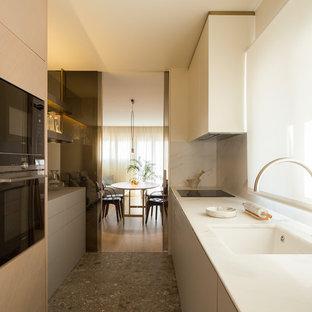 Diseño de cocina de galera, contemporánea, de tamaño medio, cerrada, sin isla, con fregadero bajoencimera, armarios con paneles lisos, puertas de armario beige, encimera de mármol, salpicadero blanco, salpicadero de mármol, electrodomésticos negros y suelo gris