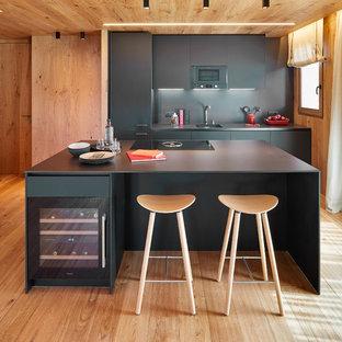 Immagine di una grande cucina minimalista con lavello a vasca singola, ante lisce, ante nere, top in pietra calcarea, paraspruzzi nero, paraspruzzi in pietra calcarea, elettrodomestici in acciaio inossidabile, isola, top nero, parquet chiaro e pavimento beige