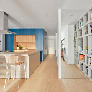 Design ideas for a contemporary u-shaped open plan kitchen in Barcelona with blue cabinets, white appliances, light hardwood floors, a peninsula, brown floor, beige benchtop, louvered cabinets, beige splashback and window splashback.