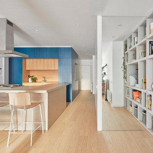 Diseño de cocina en U, contemporánea, abierta, con puertas de armario azules, electrodomésticos blancos, suelo de madera clara, península, suelo marrón, encimeras beige, armarios con puertas mallorquinas, salpicadero beige y salpicadero de vidrio