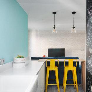 Foto de cocina de galera, actual, abierta, con fregadero sobremueble, armarios con paneles lisos, puertas de armario blancas, salpicadero azul, electrodomésticos blancos y península