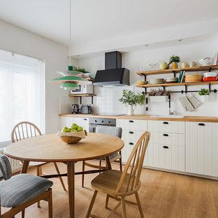 Modelo de cocina comedor nórdica con fregadero encastrado, armarios abiertos, encimera de madera, salpicadero blanco y suelo de madera en tonos medios