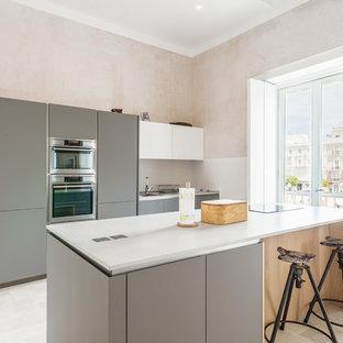 Foto de cocina mediterránea con armarios con paneles lisos, puertas de armario grises, salpicadero blanco, electrodomésticos de acero inoxidable, una isla, suelo blanco y encimeras blancas
