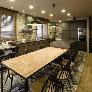 バルセロナの大きいインダストリアルスタイルのおしゃれなキッチン (フラットパネル扉のキャビネット、グレーのキャビネット、マルチカラーのキッチンパネル、セラミックタイルのキッチンパネル、シルバーの調理設備の、セラミックタイルの床) の写真