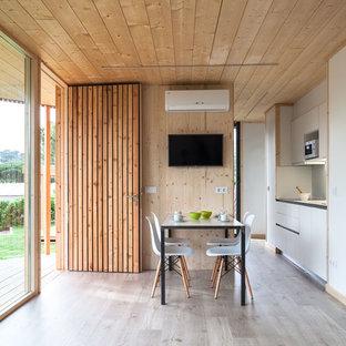 Modelo de cocina contemporánea con armarios con paneles lisos, puertas de armario blancas y suelo de madera en tonos medios