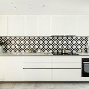 Diseño de cocina comedor actual con suelo de baldosas de cerámica, fregadero bajoencimera, armarios con paneles lisos, puertas de armario blancas, salpicadero multicolor, electrodomésticos negros, suelo gris y encimeras blancas