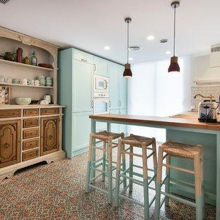 他の地域の中サイズの地中海スタイルのおしゃれなキッチン (ターコイズのキャビネット、木材カウンター、セラミックタイルの床、ドロップインシンク、白いキッチンパネル、マルチカラーの床、ベージュのキッチンカウンター) の写真