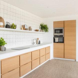 Foto de cocina en L, nórdica, con fregadero bajoencimera, armarios con paneles lisos, puertas de armario de madera clara, salpicadero blanco, electrodomésticos de acero inoxidable, suelo beige y encimeras blancas