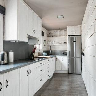 Modelo de cocina en L, urbana, con armarios con paneles lisos, puertas de armario beige, salpicadero verde, electrodomésticos de acero inoxidable, suelo marrón, encimeras grises y suelo de madera en tonos medios