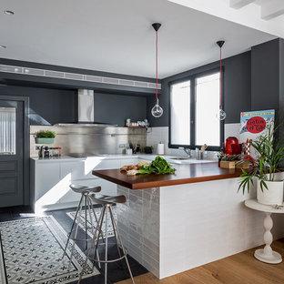 Idéer för ett avskilt, mellanstort modernt u-kök, med en undermonterad diskho, släta luckor, vita skåp, träbänkskiva, stänkskydd med metallisk yta, stänkskydd i metallkakel, klinkergolv i keramik och en halv köksö