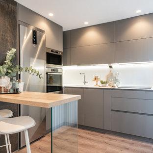Diseño de cocina en L, actual, de tamaño medio, con fregadero integrado, armarios con paneles lisos, puertas de armario grises, salpicadero blanco, electrodomésticos de acero inoxidable, península, suelo beige y encimeras blancas