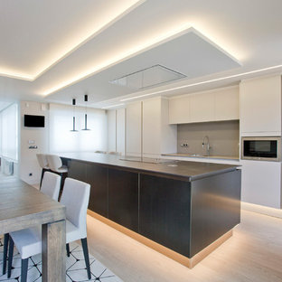 Photo of a large contemporary single-wall open plan kitchen in Other with an undermount sink, flat-panel cabinets, beige cabinets, glass benchtops, beige splashback, window splashback, stainless steel appliances, porcelain floors, with island, brown floor and beige benchtop.