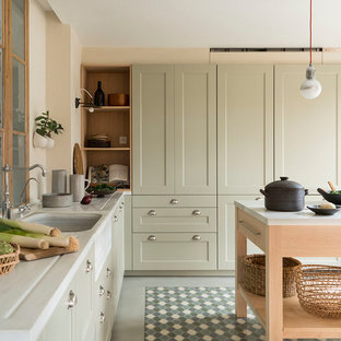 This is an example of a mid-sized mediterranean l-shaped open plan kitchen in Barcelona with raised-panel cabinets, beige cabinets, limestone benchtops, ceramic floors, with island, multi-coloured floor, grey benchtop, an integrated sink and panelled appliances.