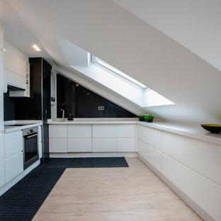 Imagen de cocina en U, contemporánea, sin isla, con armarios con paneles lisos, puertas de armario blancas, salpicadero negro y encimeras blancas