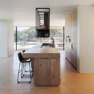 Foto de cocina mediterránea con puertas de armario de madera clara, encimera de madera, una isla y suelo beige