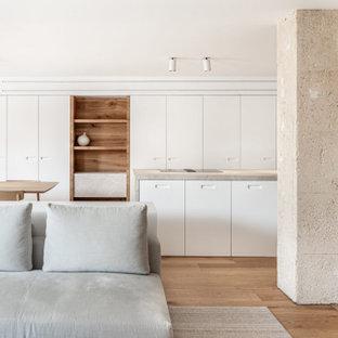 Ejemplo de cocina de galera, minimalista, abierta, con armarios con paneles lisos, puertas de armario blancas, suelo de madera en tonos medios, una isla, suelo marrón y encimeras grises